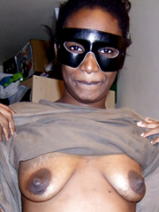 Ugly black female wearing a mask bares his saggy boobs