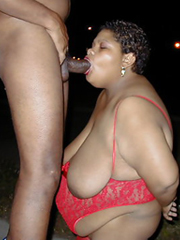 Very thick black granny takes a dick in her mouth in public